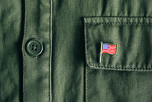 USA Flag Pin Badge On Green Jacket Pocket. Top View. Copy, Empty Space For Text