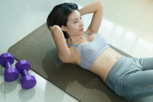 Young woman in gray sportswear exercise at home, doing abs sit ups, in quarantine during Coronavirus pandemic Wallpaper Mural