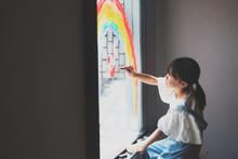 窓に虹の絵を描く少女