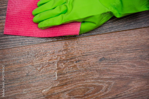 Photo Closeup of a hand in a green rubber glove rubbing a wet wooden surface