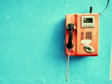 Close-up Of Landline Phone Mounted On Blue Wall