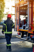 Firefighter In Protective Clothing, Helmets And Mask. Fireman  In Fire Fighting Operation.