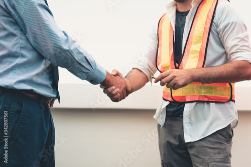 Photo Midsection Of Businessman Shaking Hands With Architect At Construction Site