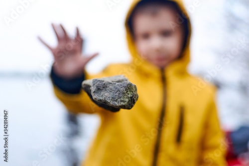 Foto A child throws a stone. The stone hangs in the air.