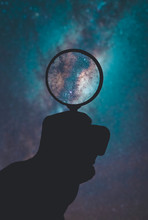 Cropped Hand Holding Magnifying Glass Against Star Space