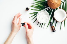 Female Hands Applying Coconut Oil For Hand Skin Moisturizing. Flat Lay Composition With Woman's Hands, Tropical Palm Leaf, Coconuts, Essential Oils. Hand Skincare, Beauty Treatment Concept