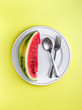 Sliced Watermelon on white plate with spoon and fork stock photo with bright background.