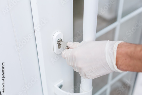 closeup of a caucasian man opening a door with a key wearing latex gloves, Hygiene concept Wallpaper Mural