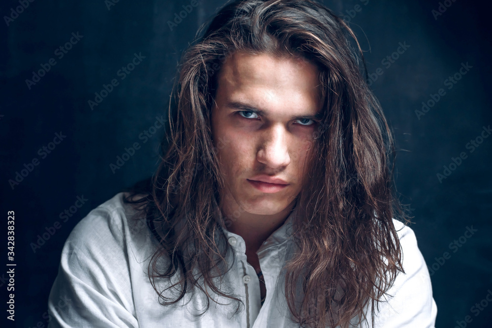 Fototapeta Handsome calm man. Portrait of a young muscular guy with long hair. Strong boy on an isolated dark background in the studio