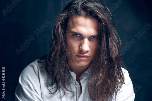 Obraz Handsome calm man. Portrait of a young muscular guy with long hair. Strong boy on an isolated dark background in the studio - fototapety do salonu