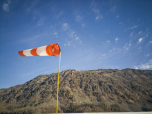 Scenic View Of Windsock Against Mountain And Sky