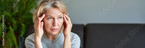 Fotografie, Tablou Woman suffering from a headache and stress holding her hands to her temples