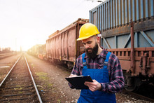 Dispatching Cargo Containers Via Railroad Freight Transportation. Shipping Worker Writing Down On Clipboard And Controlling Shipping Cargo Containers Departure. Organizing Goods Export.