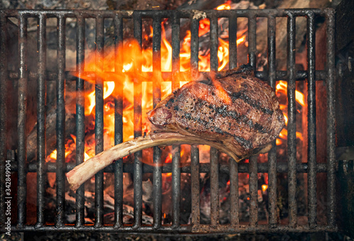 tomahawk steak cooking on flaming grill Tableau sur Toile