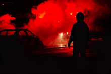 Rear View Of Silhouette Man Standing By Smoke On Illuminated Street At Night