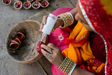 Indian Woman In Traditional Costume Decorating And Painting A Small Clay Bowl