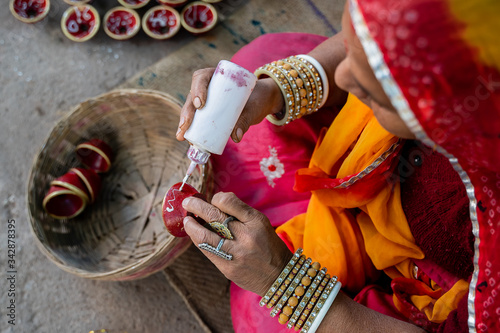 Obraz Indian woman in traditional costume decorating and painting a small clay bowl  - fototapety do salonu