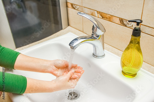 Photo A Hands with soap are washed under the tap with water