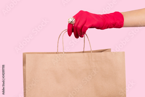 Womans hand in a rubber glove holding paper bag on pink background Canvas Print