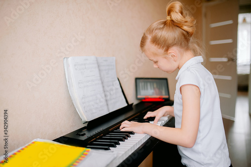 Fotografie, Tablou schoolgirl studying notes and playing the classic digital piano while watching