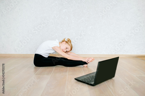 Papel de parede Schoolgirl watching online video on laptop and doing sports exercises - yoga, gymnastics, choreography