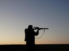 Silhouette Of Man Holding Sniper Against Sky During Sunset
