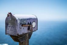 Close-up Of Public Mailbox Against Sea