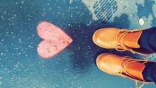 Low Section Of Woman Wearing Orange Shoes By Heart Shape On Wet Street