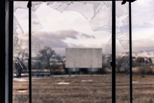Field Against Sky Seen Through Broken Glass Window