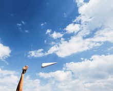 Cropped Image Of Hand Flying Paper Airplane Against Sky