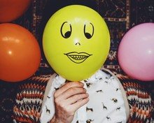 Close-up Of Man Holding Yellow Smiley Balloon