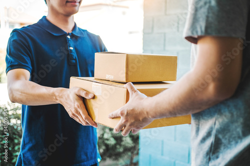 Obraz na plátně Delivery concept Asian Man hand accepting a delivery boxes from professional del