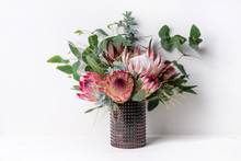 A Elegant Floral Arrangement In A Rustic Brown Vase On A Table With A White Background. Flower Bunch Includes A Pink King Protea, Pink Ice Proteas, Leucadendrons, Wattle Leaves And Eucalyptus Leaves.
