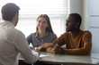 Young successful couple, diverse man and woman listening manager at negotiating. Happy smiling african american husband and wife making deal in broker office. Businessman holds meeting with customers