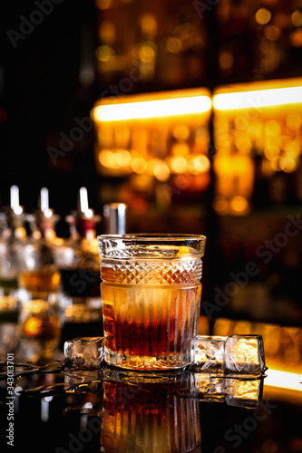 A cocktail in an old fashioned glass on a bar counter with a reflection, ice cub Canvas Print