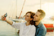 Young smiling couple in love makes selfie portrait with phone. Romantic concept