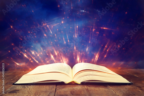 Fototapety, obrazy: image of open antique book on wooden table with glitter overlay