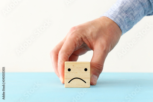 male hand holding wooden cube with sad face Fototapet
