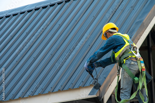 Construction worker wearing safety harness belt during working on roof structure of building on construction site,Roofer using air or pneumatic nail gun and installing metal roof tile on top new roof Fototapet