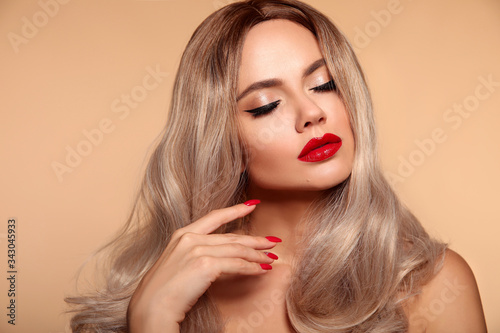 Fototapety, obrazy: Makeup, manicured nails. Beauty portrait of blonde woman with red lips, long healthy shiny blond hair style. Sensual girl with bright makeup isolated on beige backhround.