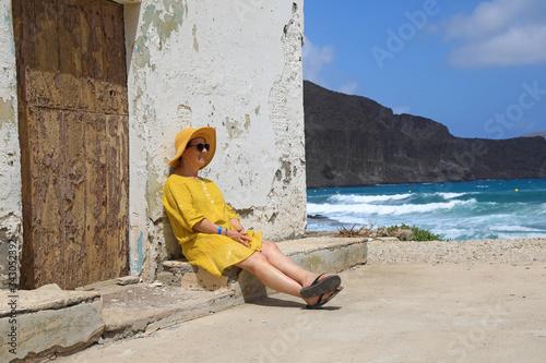 mujer con sombrereo amarillo y vestido amarillo sentada casa playa mediterraneo Canvas Print