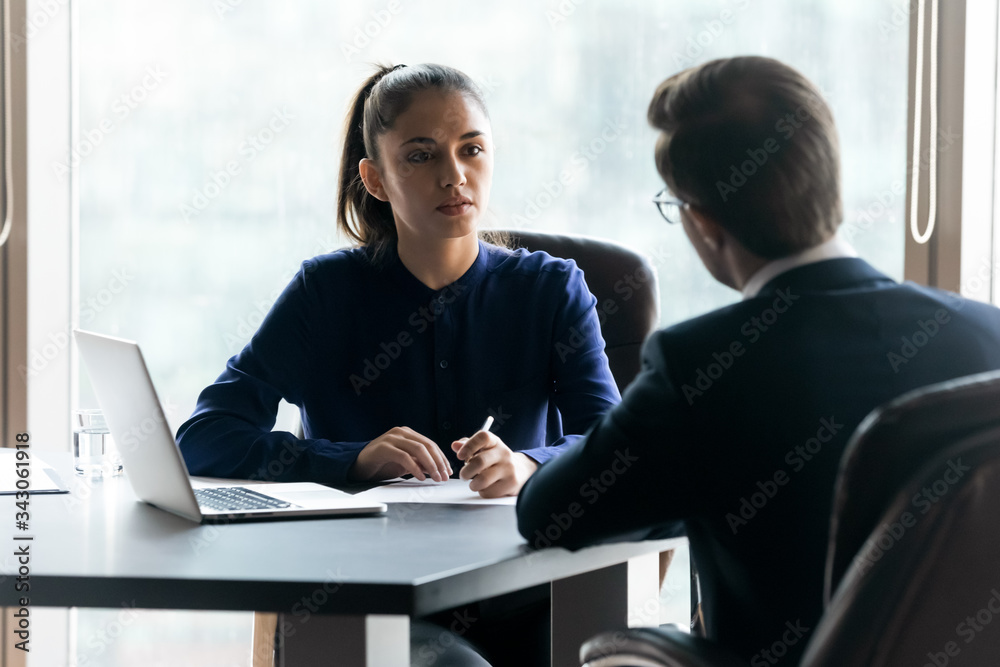 Fototapeta Confident attentive businesswoman hr manager listening to candidate answering questions on job interview, focused recruiter employer looking at applicant, sitting at desk in office
