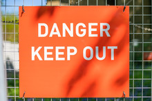 Close Up Of A Red Danger Keep Out Sign In Bright Sunny Sunlight