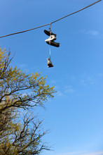 Sneakers Hanging On The Power Line. Dangling Shoes Have Meaning.