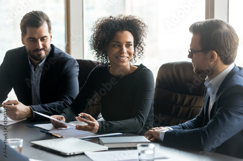 Smiling African American businesswoman speaking at corporate meeting in boardroom, sitting at table, business partners discussing contract terms, colleagues sharing ideas at briefing