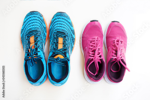 Photo Pair of men's blue sneakers and pair of women's pink sneakers on white background