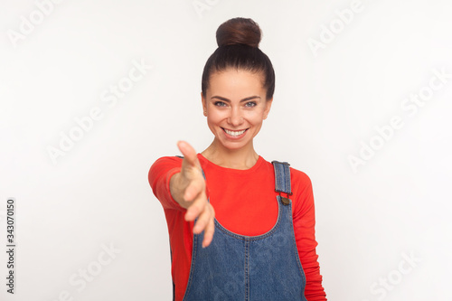 Nice to meet you! Portrait of friendly stylish pretty girl with hair bun in denim overalls giving hand to handshake, getting acquaintance, meeting with smile Wallpaper Mural