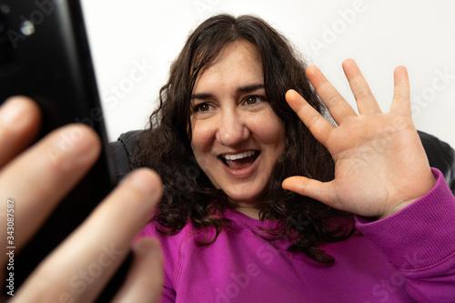 Photo Señora blanca de edad media saluda en una videollamada con cara alegre sonriendo y con la mano abierta