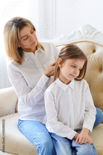 Mom straightens her daughter's hair Canvas Print