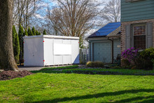 White Storage Pod Unit In The Driveway Of A Home That Has Solar Panels